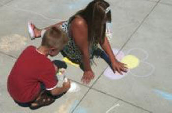 Kristen McEachron and her brother Garrett draw sidewalk pictures at the Thousand Oaks Library.